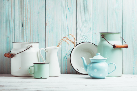 Enamelware on the kitchen table over blue wooden wall