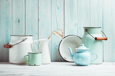 Enamelware en la mesa de la cocina a través de la pared de madera azul