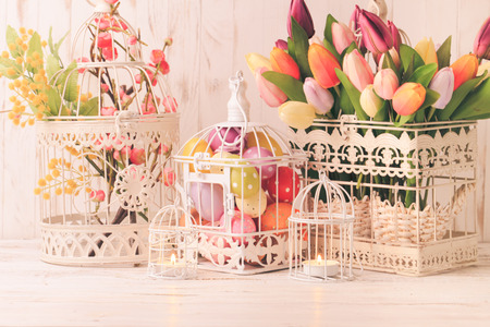 easter candle is burning: Easter decorations - shabby chic birdcages with flowers and eggs