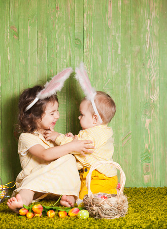 Little boy and girl as a Easter rabbits on the grass with colorful eggs