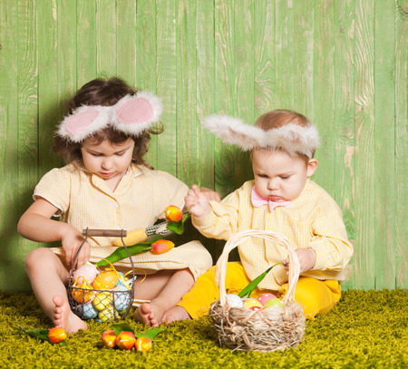 Little boy and girl as a Easter rabbits on the grass with colorful eggs photo