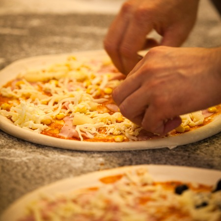 Making Pizza in restaurant, close up hands of chef Stockfoto