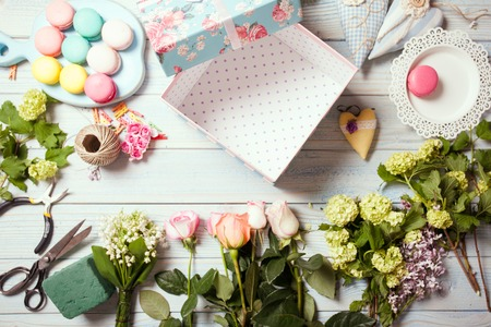 Box with flowers and macaroons on wooden table photo