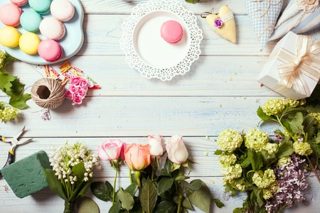 Box with flowers and macaroons on wooden table