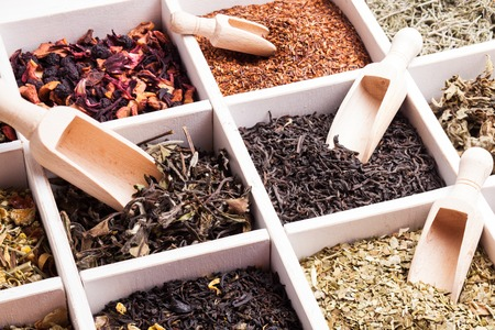 Various tea in a wooden box and scoops Stockfoto