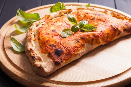 Pizza calzone with basil leaves close up