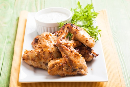 tzatziki: Roasted Chicken wings and tzatziki sauce on a plate