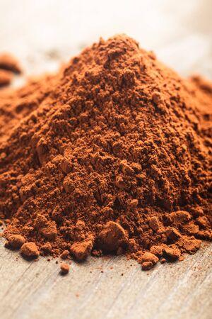 chocolate powder: chocolate powder heap over a wooden background