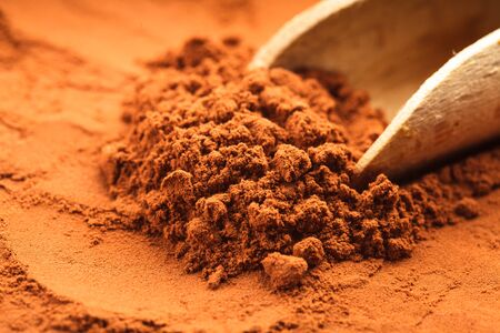 chocolate powder: chocolate powder heap and wooden scoop close up