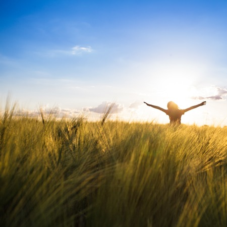 Teenage girl enjoy with sunshine in wheat field 스톡 콘텐츠