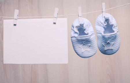 Baby boy booties attached to the rope and blank card for greetings
