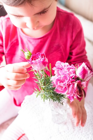 smelling: Little girl is smelling the roses. Close up face