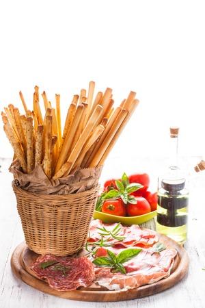 grissini: Grissini sticks and meat antipasto - italian appetizer