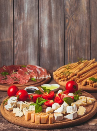 grissini: Italian appetizer - various types of ham, cheese and grissini with copy space on the wall