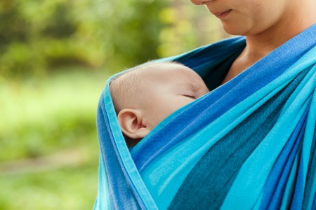 Baby is sleeping in sling, close up face