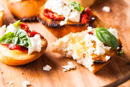 queso de cabra: Bruschetta con aceite de oliva, tomates secos, queso feta y albahaca fresca Foto de archivo