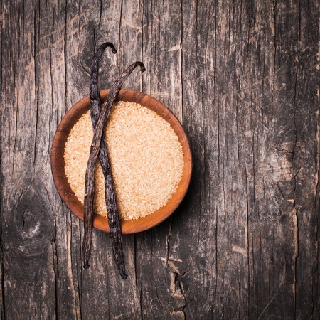 Vanilla sugar in a wooden bowl on a rustic background. Two vanilla pods on brown sugar