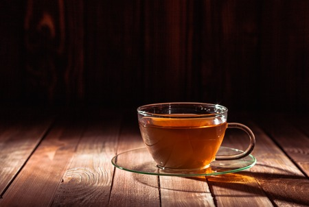 herbal background: Glass cup of tea on a wooden table