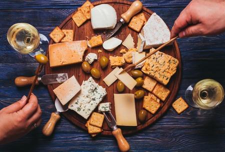queso de cabra: Par tiene una tarde agradable con plato de queso y vino Foto de archivo