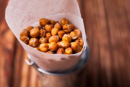 indian cookery: Spicy baked chickpeas in a metal pail on the wooden background Stock Photo