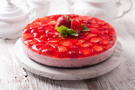 Strawberry cake on white wooden plate with mint leaf Foto de archivo