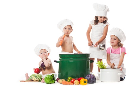 bebe sentado: Cuatro niños juegan con verduras y utensilios de cocina, cocinar la sopa Foto de archivo