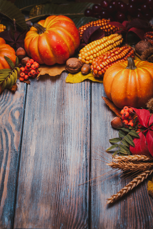 Thanksgiving still life - berries, nuts, corn and pumpkins on a table Stock Photo
