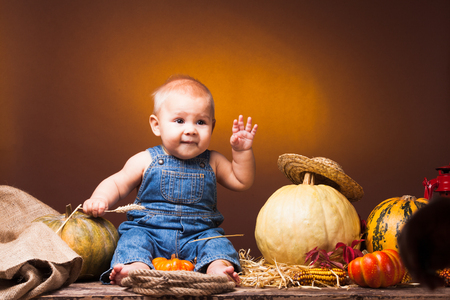 fall harvest: Cute baby with ears of wheat in the hands posing on the background of pumpkins.