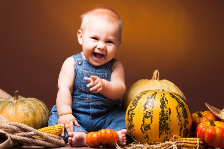 autumn harvest: Cute baby posing on the background of pumpkins. Thanksgiving greetings