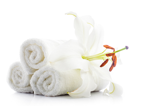 spa flower: White spa towels with lily flower isolated on white Stock Photo