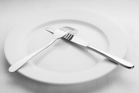 Fork and knife lying on the empty white plate Stock Photo
