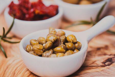 alcaparras: Alcaparras marinados en un plato blanco sobre una tabla