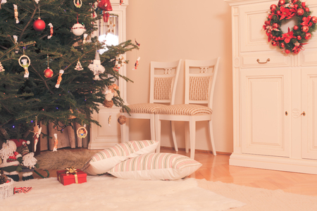 indoor background: Christmas tree with presents underneath  of Santa Claus and two pillows lying along