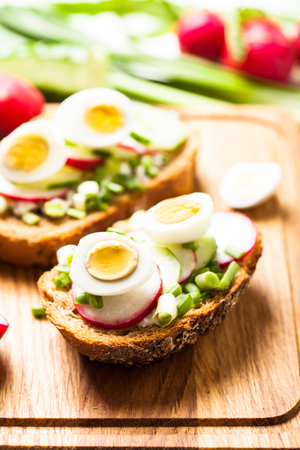 Sandwiches with fresh radish, cucumber, onions and quail eggs on a wooden table
