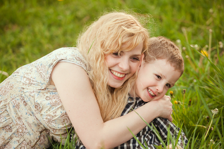 little boy and girl: Portrait of a happy mother hugging her little son on the grass