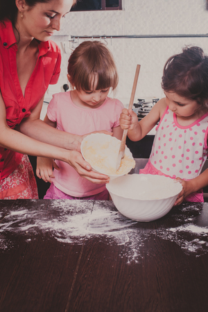 caucasion: Mom is baking cookies with her kids at home kitchen
