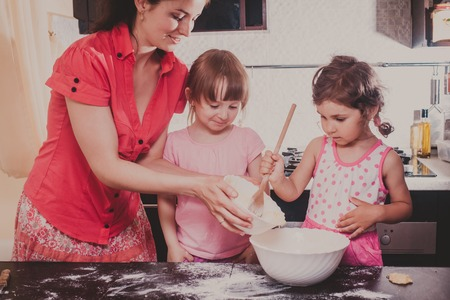 baking ingredients: Mom is baking cookies with her kids at home kitchen