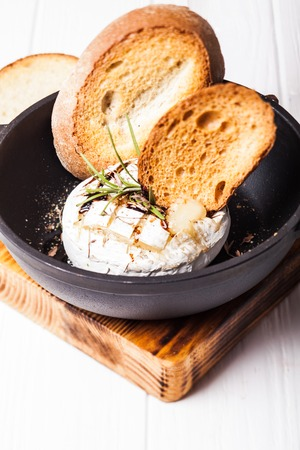 repast: Baked camembert with herbs and spices on the pan