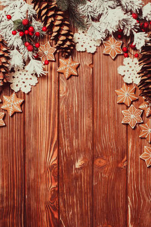 festive food: Frame of gingerbreads and winter decor on a wooden background.