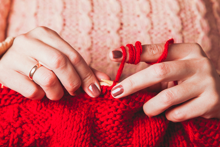 warm jacket: The hands that hold needles and knitting a red warm jacket Stock Photo