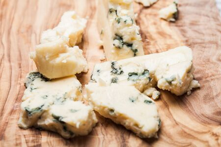 crumbled: Blue cheese close up on olive wooden board