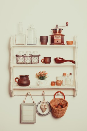 vintage dishware: White kitchen shelves in rustic style with kitchenware on the white wall Stock Photo