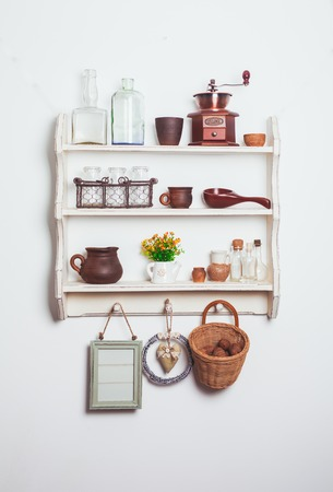 White kitchen shelves in rustic style with kitchenware on the white wall Stockfoto