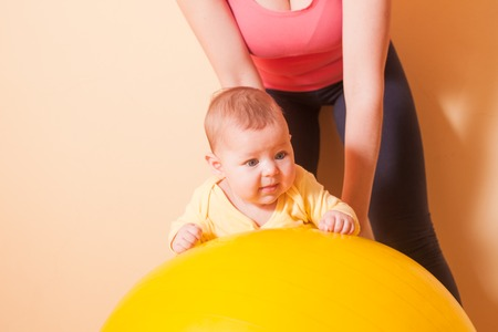fitball: Caring mother doing sport exercises with her baby on fitball Stock Photo