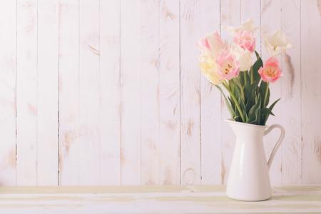 tulipan: Biały wazon z delikatnymi cieniami naręczem tulipanów na tle drewniane