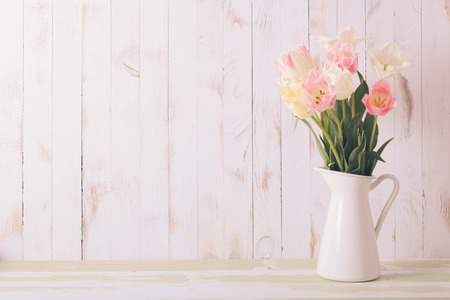White vase with delicate shades armful of tulips on a wooden background Stockfoto