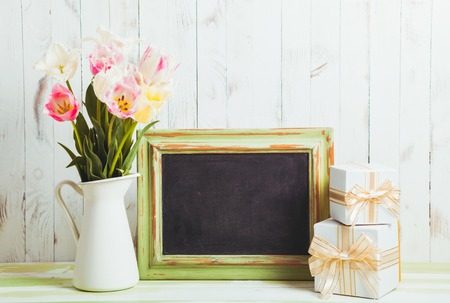 teacher: Pink tulips in jug and green wooden chalkboard. Teachers day concept Stock Photo