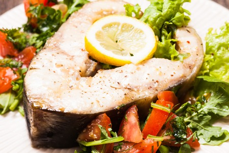 sturgeon: The sturgeon steak with salad and lemon on the plate