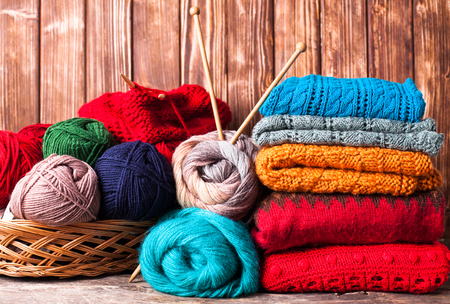 cotton fabric: Color threads, knitting needles and clothes on the wooden table