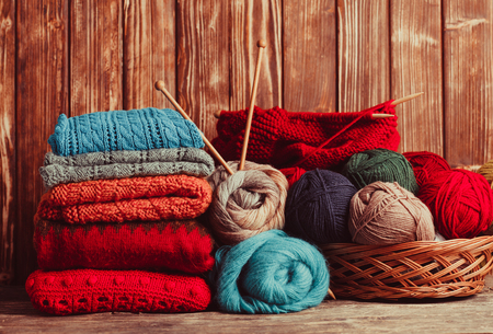 winter clothes: Color threads, knitting needles and clothes on the wooden table